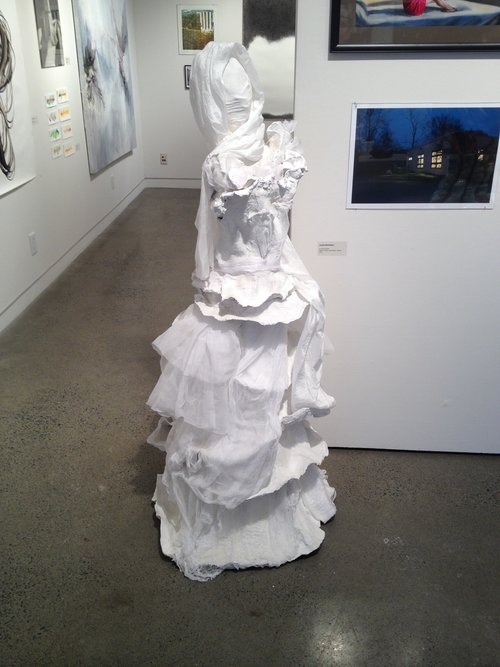 This is a paper mache, clay, and lace white dress by Sophie Mendelson.